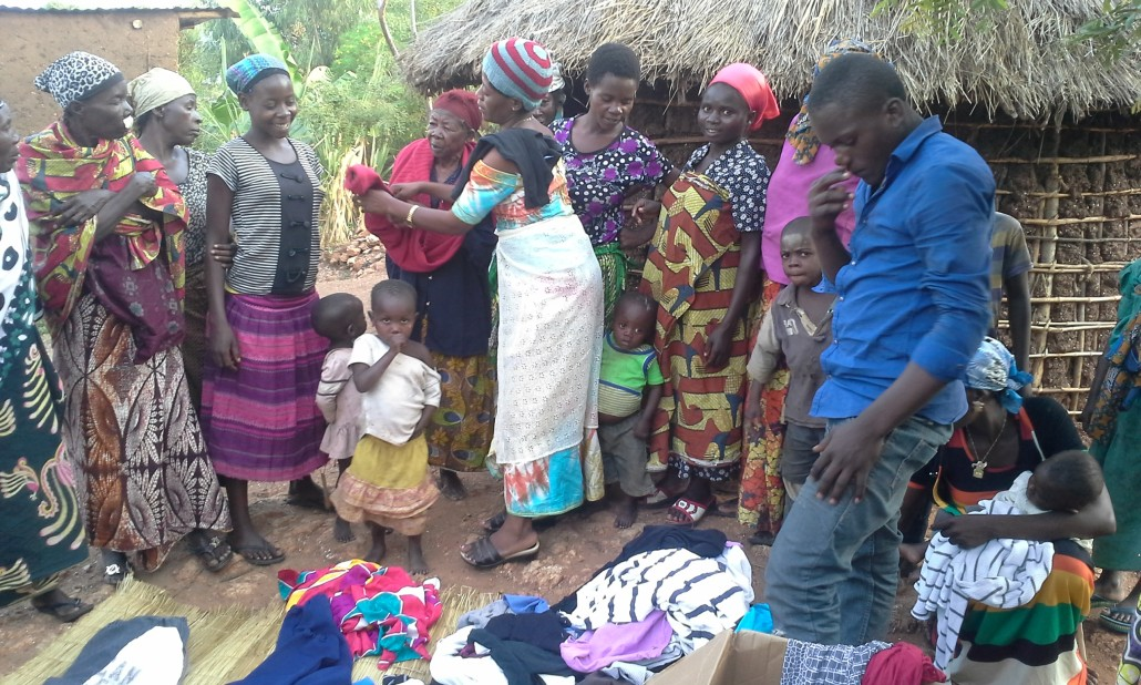 Mwanebana (in blue shirt), a student at the orphanage and Sophia (caretaker) distribute clothes to widows and their families.